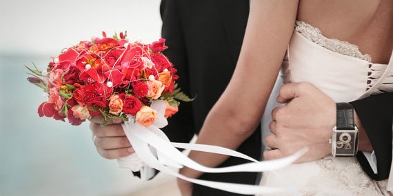 Bride and groom hold each other after the wedding with bouquet in hand