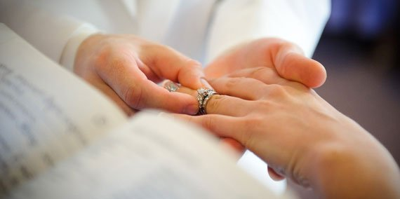 Groom putting wedding ring on bride during chapel wedding
