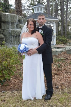 Erin Cooper and Robert Love stand near a waterfall after their gazebo wedding
